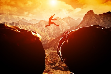 Man jumping over precipice between two mountains at sunset